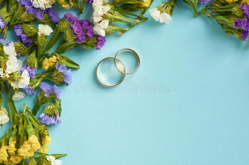 Golden rings with colored flowers on blue background composition, wedding template. Flat lay and top view photo, love, circle, border, frame, leafs, layout stock photo