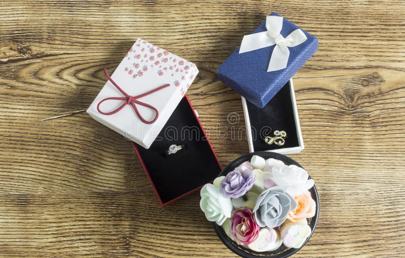 Golden rings lie in a red and blue boxes with many button roses on wooden table. stock images
