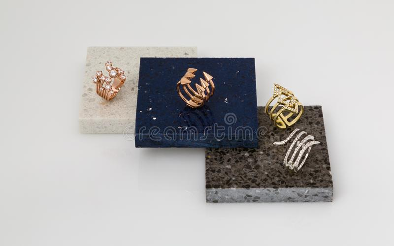 Golden and silver rings set on stone pieces. Golden rings set on stone plates royalty free stock photography