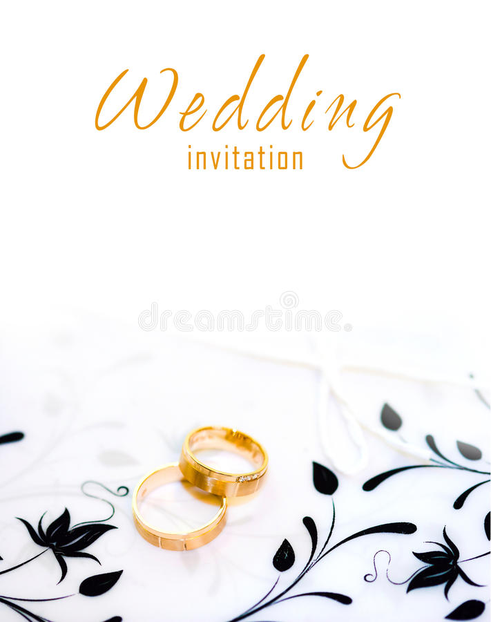 Golden rings on a wedding invitation. With floral decoration stock photography
