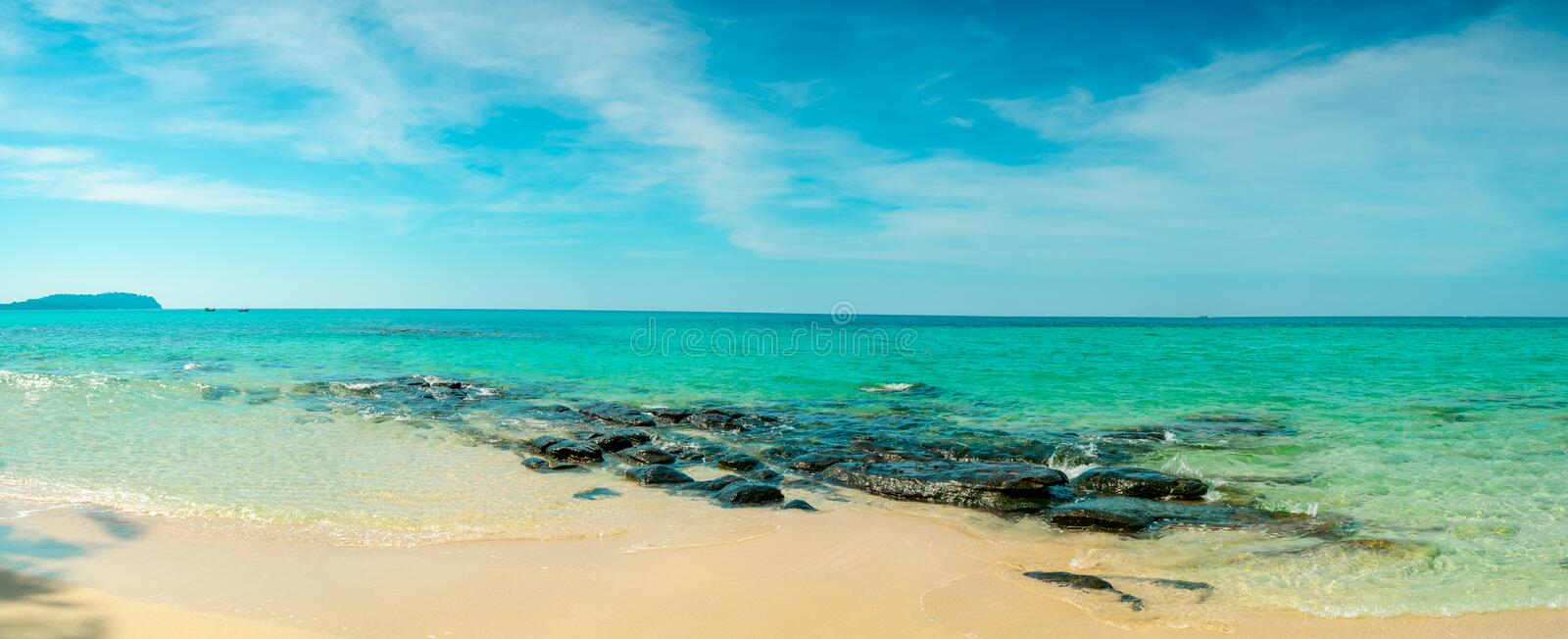 Golden sand beach by the sea with emerald green sea water and blue sky and white clouds. Summer vacation on tropical paradise stock images