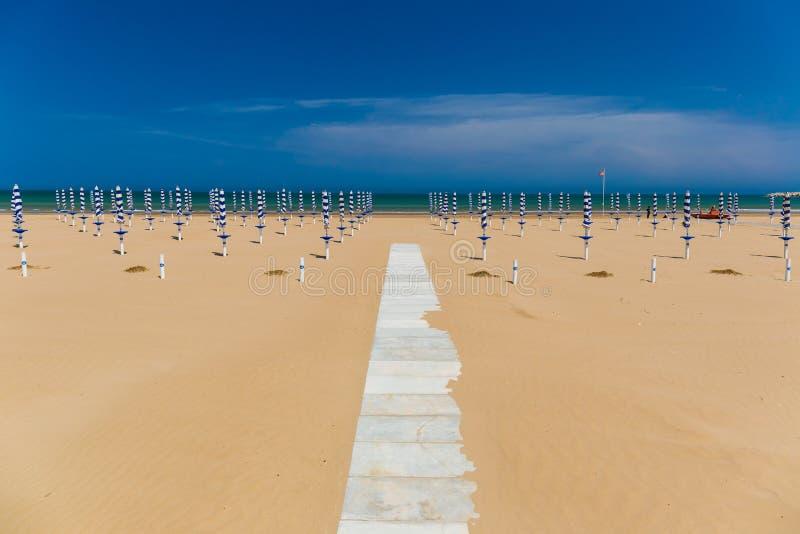 Golden sand beach of Vieste, Gargano peninsula, Apulia, South of Italy. Golden sand beach of Vieste with path towards the sea and umbrellas, Gargano peninsula royalty free stock images