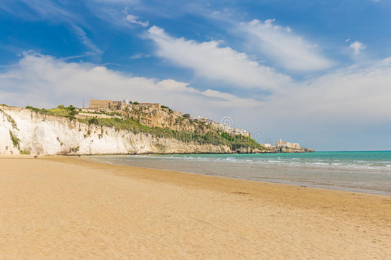 Golden sand beach of Vieste with Pizzomunno rock, Gargano peninsula, Apulia, South of Italy. Golden sand beach of Vieste with Pizzomunno rock, typical white royalty free stock photography