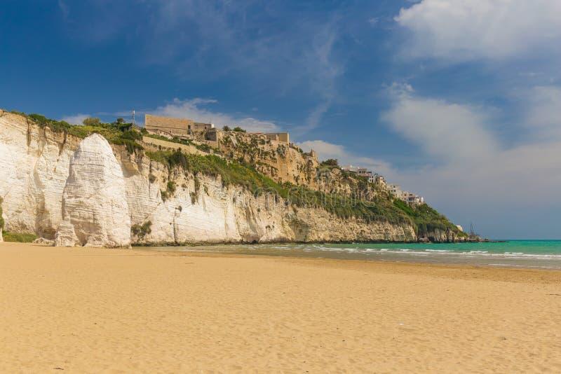 Golden sand beach of Vieste with Pizzomunno rock, Gargano peninsula, Apulia, South of Italy. Golden sand beach of Vieste with Pizzomunno rock, typical white stock image