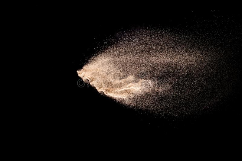 Golden sand explosion isolated on black background. Abstract sand cloud. stock image
