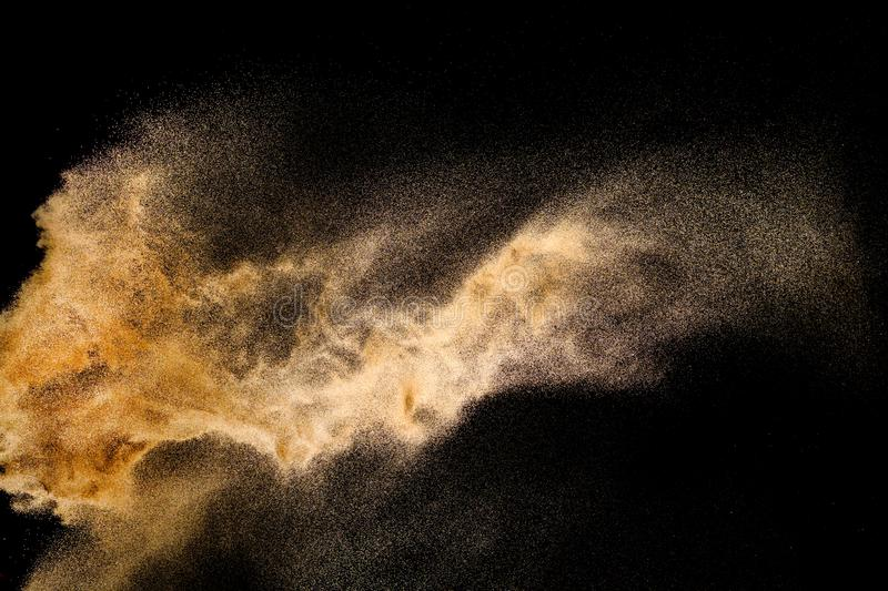 Golden sand explosion isolated on black background. Abstract sand cloud. Golden colored sand splash against dark background. Yellow sand fly wave in the air royalty free stock photo