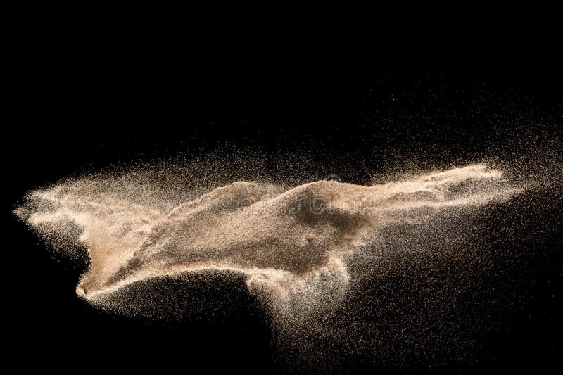Golden sand explosion isolated on black background. stock images