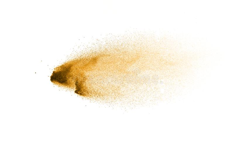 Golden sand explosion isolated on white background. Abstract sand splashing stock images