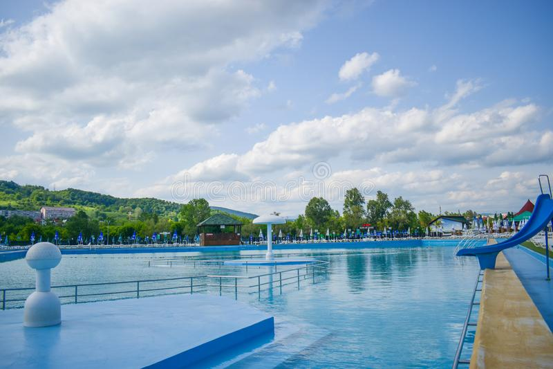 Golden sand and white beach chairs with umbrella around the big swimming pool in Strand Ostroveni from Ramnicu Valcea. Romania - royalty free stock images