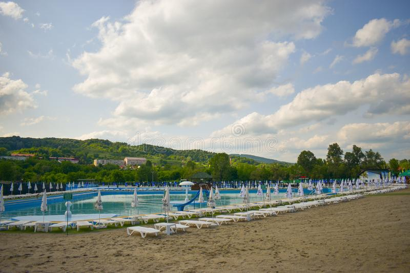 Golden sand and white beach chairs with umbrella around the big swimming pool in Strand Ostroveni from Ramnicu Valcea. Romania - royalty free stock photos