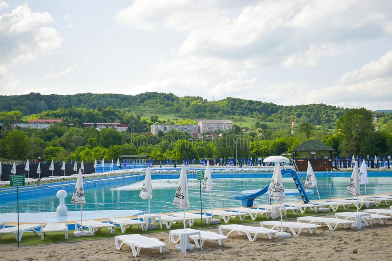 Golden sand and white beach chairs with umbrella around the big swimming pool in Strand Ostroveni from Ramnicu Valcea. Romania - stock photo