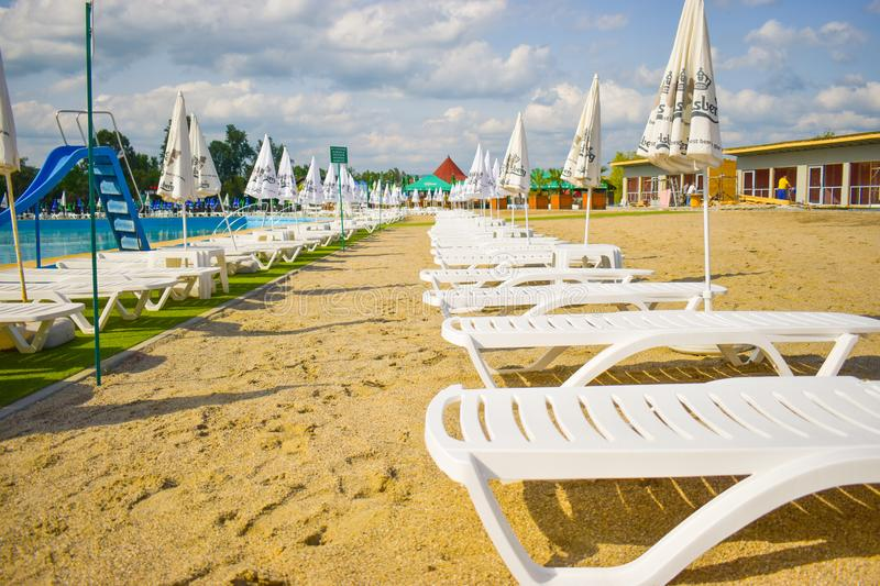 Golden sand and white beach chairs with umbrella around the big swimming pool in Strand Ostroveni from Ramnicu Valcea. Romania - stock image