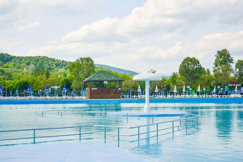 Golden sand and white beach chairs with umbrella around the big swimming pool in Strand Ostroveni from Ramnicu Valcea. Romania - stock photography