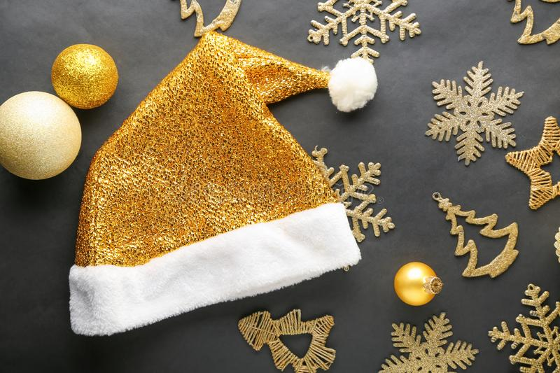 Golden Santa Claus hat with Christmas decorations on black background stock photography