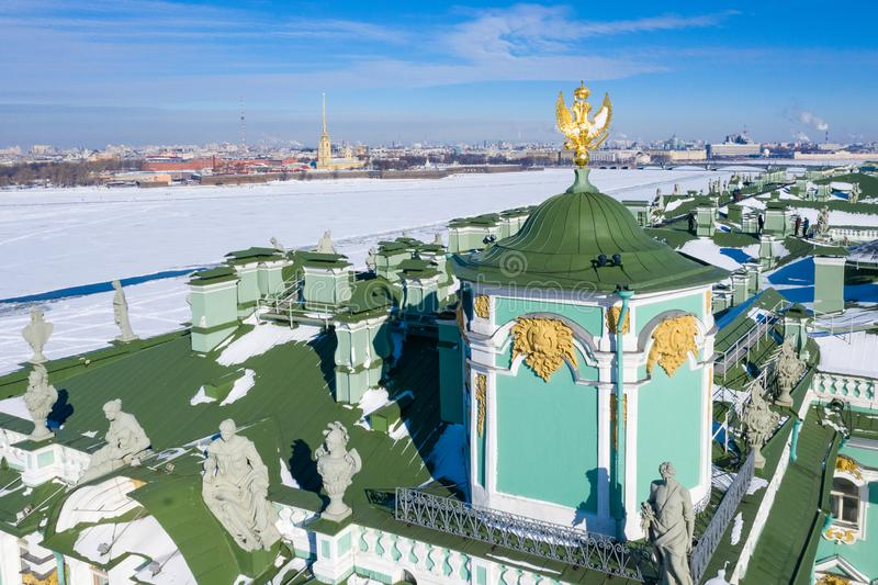 Golden sculpture of a majestic eagle of Russia on the roof of the Winter Palace in Saint-Petersburg. Symbol of the Russian Empire. Panoramic view of the city royalty free stock image
