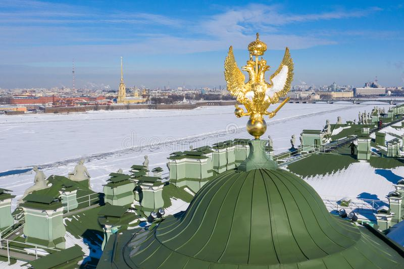 Golden sculpture of a majestic eagle of Russia on the roof of the Winter Palace in Saint-Petersburg. Symbol of the Russian Empire. Panoramic view of the city royalty free stock photo