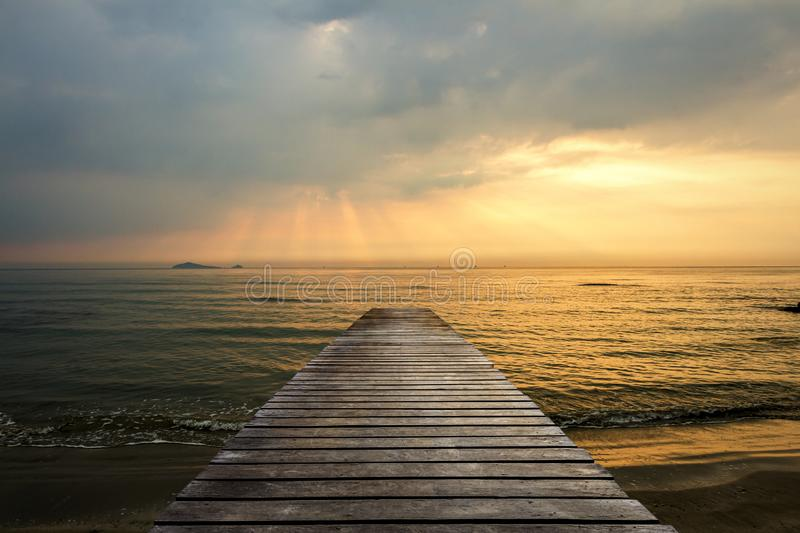 Golden sea sunset view of pier or jetty in the tropical in the summer.  stock photo