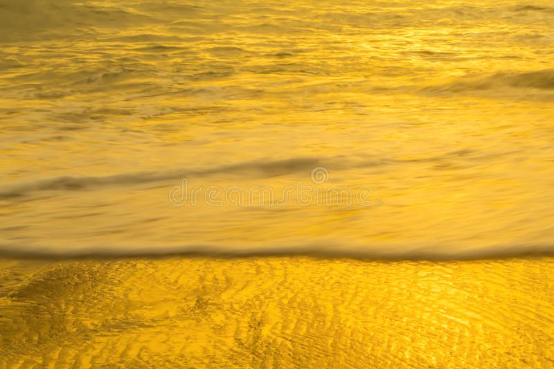 Golden sea and wave with reflect from sunset summer wallpaper b. Ackground royalty free stock photography