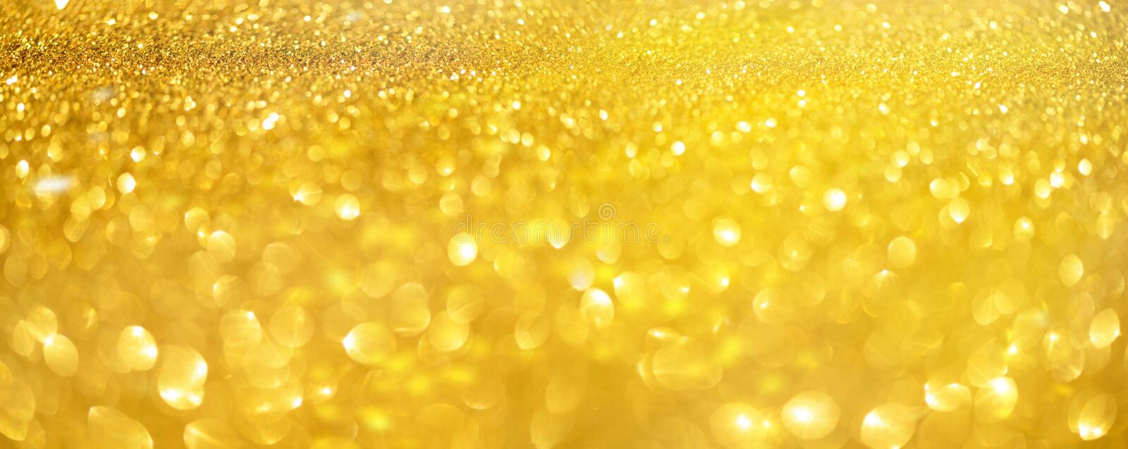 Golden shiny background, copy space for your Christmas greetings. Banner with defocused lights, bright yellow bokeh. Shimmer of. Gold glitter texture. Concept royalty free stock images