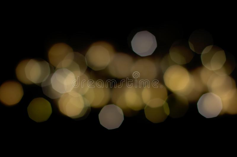 Golden shiny bokeh on black background. Abstract black and gold glitter royalty free stock photos