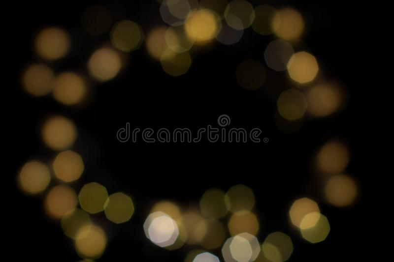 Golden shiny bokeh frame on black background. Abstract black and gold glitter stock photo