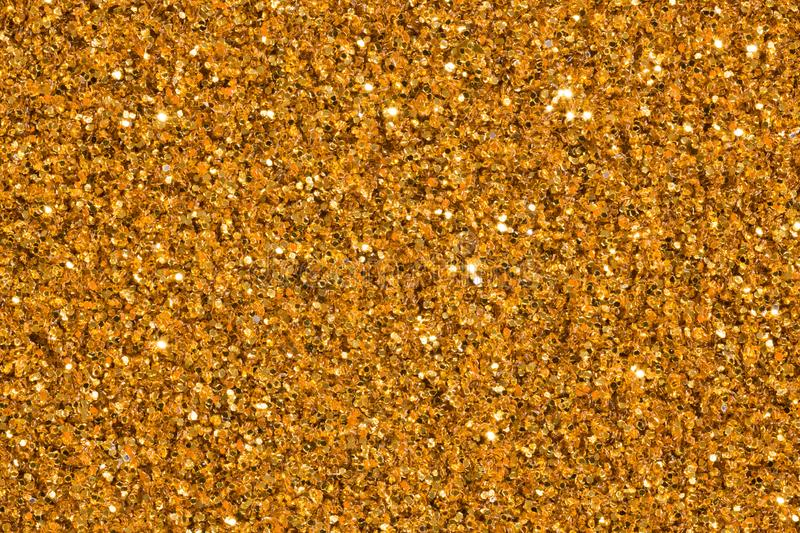 Golden shiny glitter background with glow. Golden glitter texture. royalty free stock photos