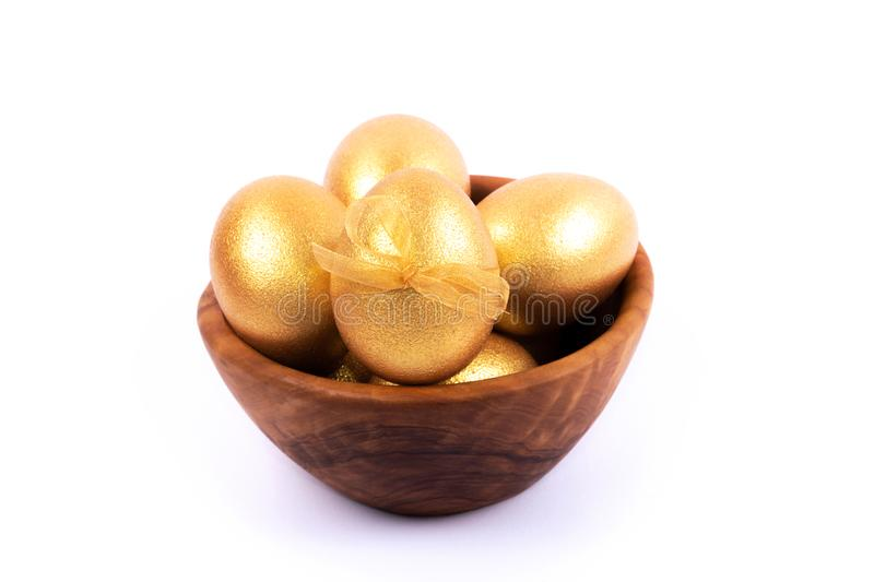Golden and silver colored Easter eggs in wooden bowl isolated on white background. Place for text. royalty free stock photos
