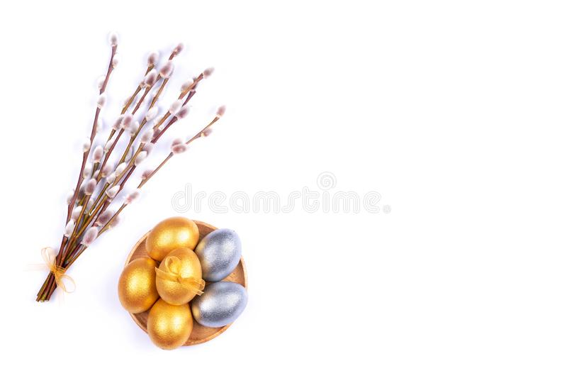 Golden and silver colored Easter eggs on wooden plate with willow catkins branches isolated on white background. Place for text. stock photography