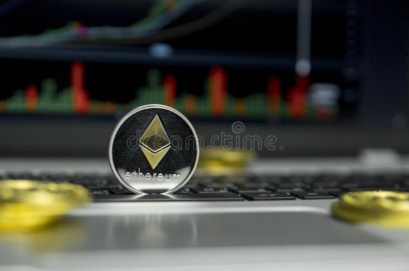 Golden Silver Ethereum coin with gold coins lying around on a black keyboard of silver laptop and diagram chart graph on. A screen as a background. Mining of stock images
