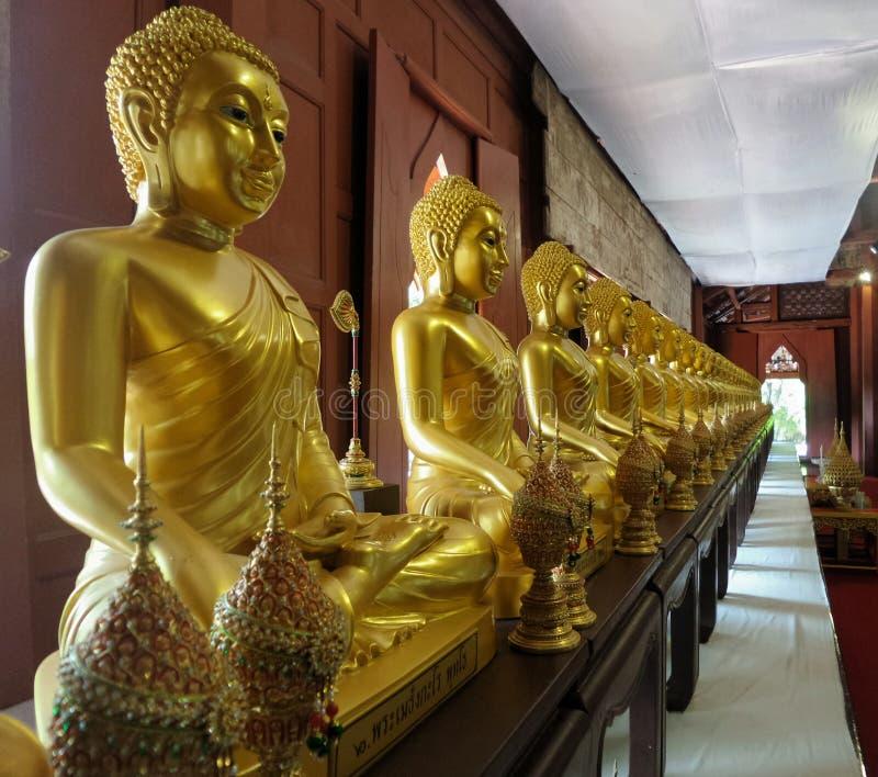 Golden sitting Buddha sculpture line in the pavillion royalty free stock photos