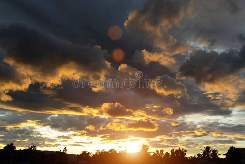 Golden sky in the evening time. Beautiful clouds with colorful sky during sunset. Abstract sun beam line light shining through the clouds stock image