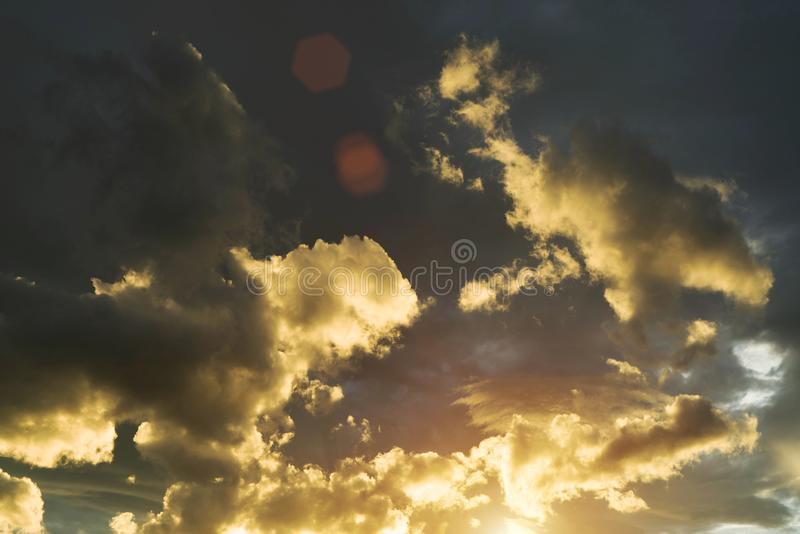 Golden sky in the evening time. Beautiful clouds with colorful sky during sunset. Abstract sun beam line light shining through the clouds stock photography