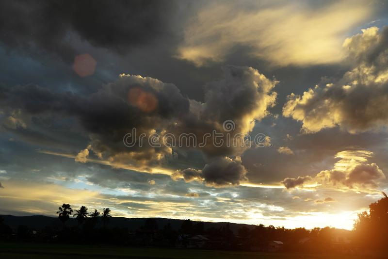 Golden sky in the evening time. Beautiful clouds with colorful sky during sunset. Abstract sun beam line light shining through the clouds royalty free stock photos
