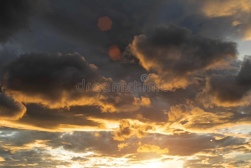 Golden sky in the evening time. Beautiful clouds with colorful sky during sunset. Abstract sun beam line light shining through the clouds royalty free stock images