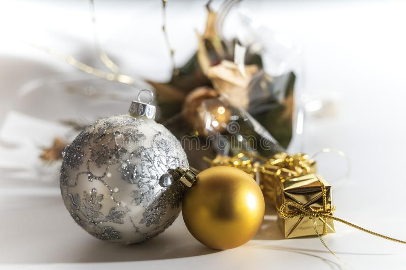 Golden and sliver christmas ball with a golden gift and blurry background stock images