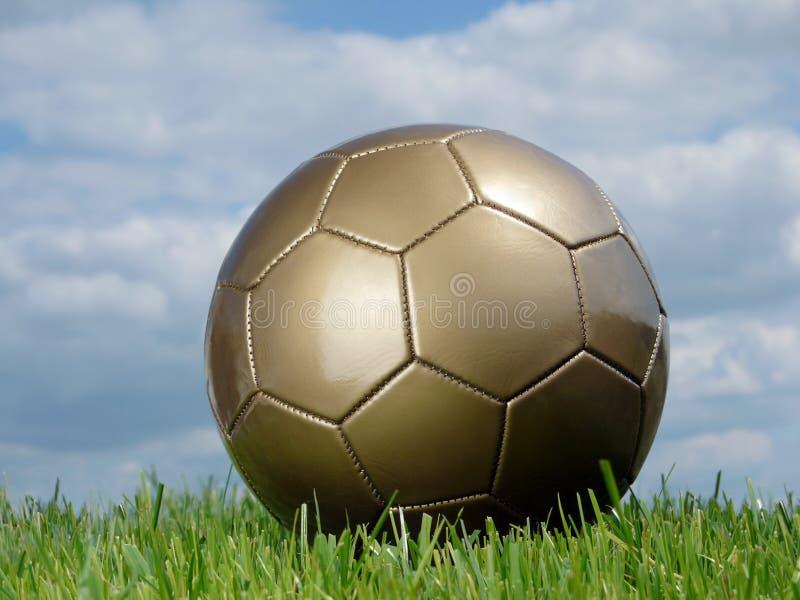 Golden soccer ball. In the grass shot against the sky stock image