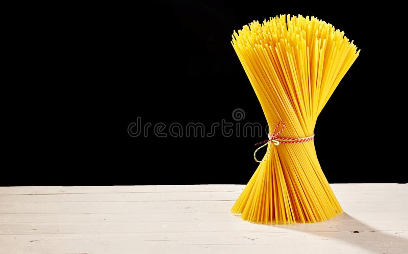 Bunched spaghetti on table with black copy space stock images