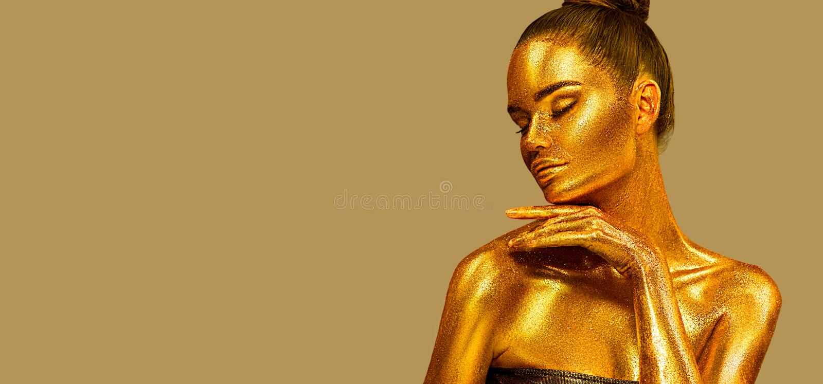 Golden sparkles skin, Woman face portrait closeup. Model girl with holiday golden Glamour shiny professional make up. Gold jewellery, jewelry, accessories stock photo