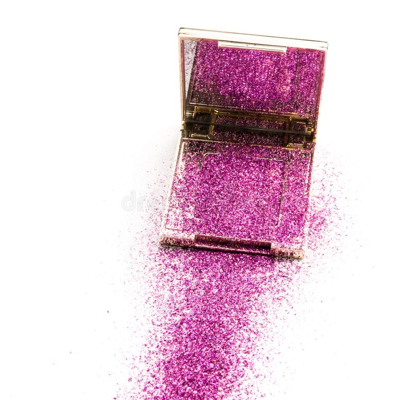 Golden square box for cosmetics with pink gloss, scattered in the form of a track. stock photo
