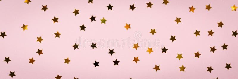 Golden star sprinkles on pink. Festive holiday background. Celeb royalty free stock photography
