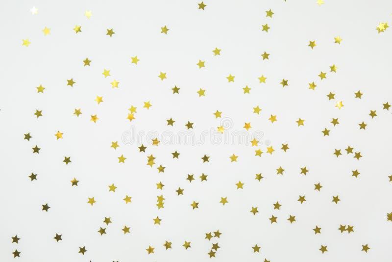 Golden star sprinkles on white. Festive holiday background. Celebration concept stock photo