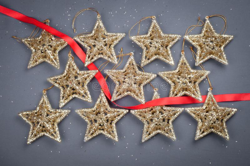 Golden stars Christmas decorations on a gray background with red ribbon. Golden stars Christmas decorations on a gray background with a red ribbon exactly lying stock images