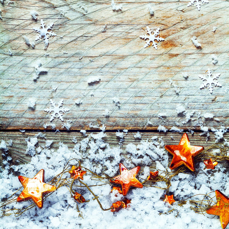 Golden stars with snow in a rustic Xmas background. Golden stars with snow and falling snowflake decorations in a rustic Xmas background with copyspace for your royalty free stock image