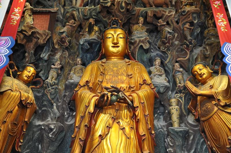 Golden Statue of Guanyin and Sudhana acompanied by their masters from the Jade Buddha Temple interior in Shanghai. Details from Golden Statue of Guanyin and stock image