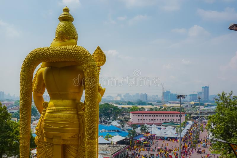 Golden statue of Lord Murugan at the entrance to the Batu cave and beautiful panorama of city royalty free stock photos