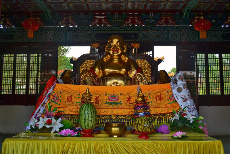 Golden Statue and offerings in Traditional Chinese Buddhist temple in Lumbini, Nepal. Birthplace of Buddha Siddhartha Gautama stock image