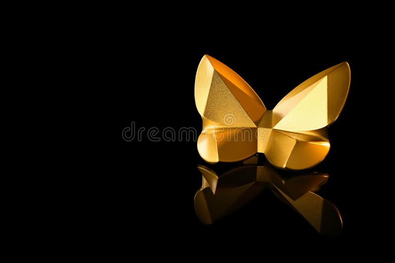 Golden statuette of butterfly on black background stock image