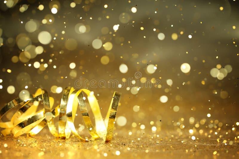 Golden streamers and glitter confetti. Closeup stock photo