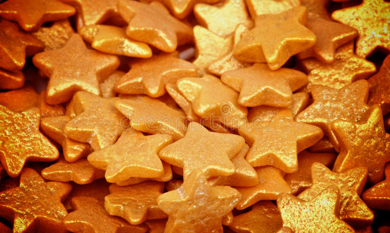 Golden Sugar Stars. Background of Golden Sugar Stars Dessert Toppings closeup. Focus on Centre royalty free stock image