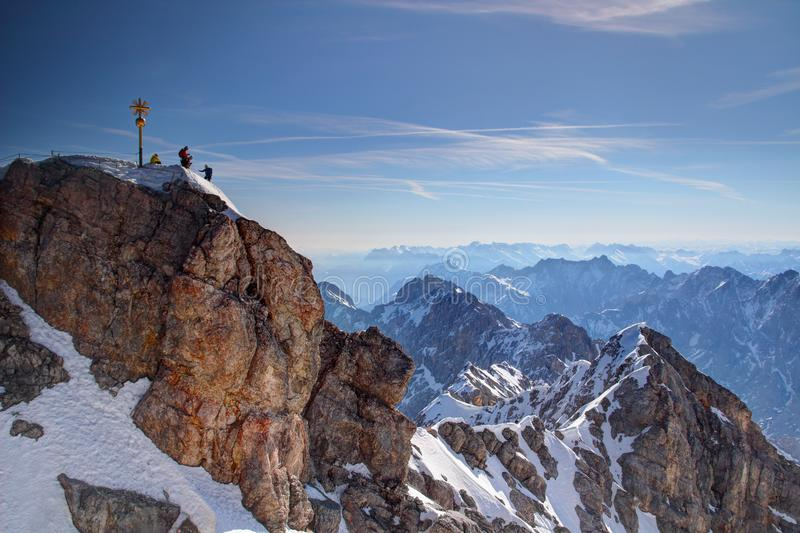 Golden summit cross and tiny climbers on top of Zugspitze peak royalty free stock image